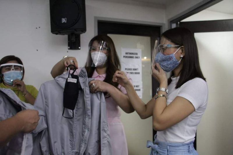 LOCAL WEAR. Angeleña designer Rosette Ramos-Biag shows Executive Assistant IV Reina Manuel and Angeles City Tourism Office consultant Cecille Flores-Sanchez one of the PPEs made through the city's livelihood program. (Angeles City Information Office)