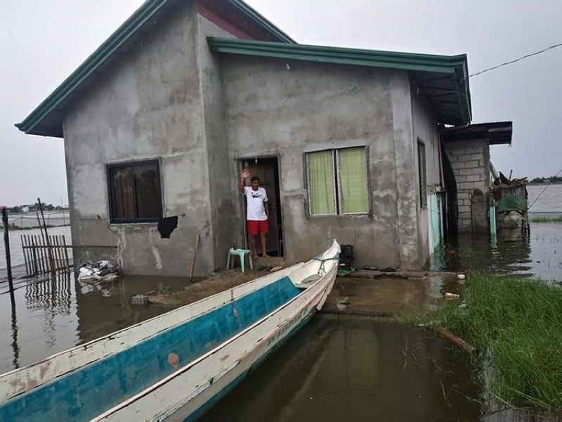 STILL JOLLY UNDER WATER. A man from Masantol town in pampanga manages to keep jolly despite his house under water. (Contributed photo)
