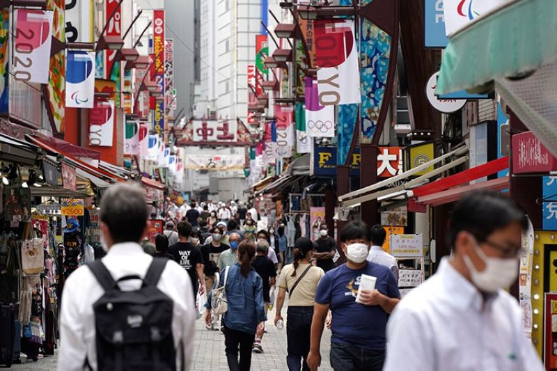 JAPAN. People wearing face masks to help curb the spread of the coronavirus walk across a shopping alley near Ueno Station in Tokyo Friday, July 30, 2021. (AP)