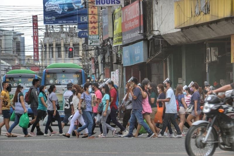 CEBU. Pedestrians wear face masks and face shields, albeit improperly, as they cross Colon St. in Cebu City. (Amper Campaña)