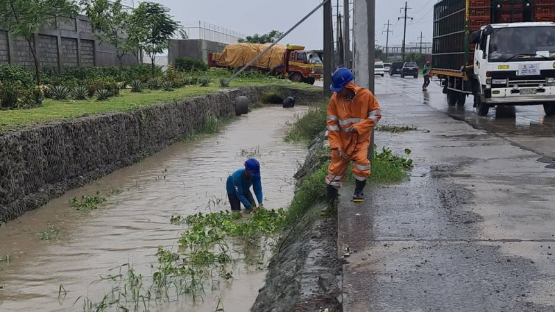 DECLOGGING EFFORT. Workers of a steel firm in san Simon town remove weeds and trash to preserve the free flow of floodwaters along drainage systems in Quezon Road. (Chris Navarro)