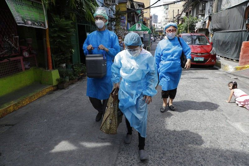 MANILA. In this photo taken in May 2021, health workers in protective suits walk to the homes of residents who are not able to go to vaccination centers in Manila. (File)
