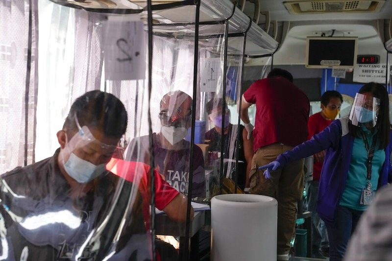 MANILA. In this photo taken in June 2021, people wearing face mask and face shield wait inside a bus being used as a mobile Covid-19 vaccination center in Taguig City. (File)