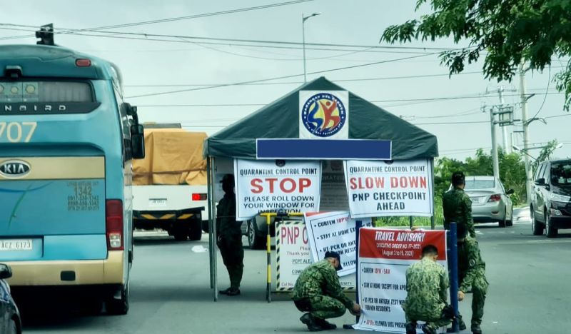QUARANTINE CONTROL POINT. Policemen put up reminders for motorists passing the NLEX San Fernando exit as non-residents are required to present a negative RT-PCR test result before entering cities and towns in Pampanga following strict travel advisory from August to 2 to 15, in compliance of EO 17 issued by Governor Dennis Pineda for additional safety protocols under MGCQ to prevent the spread of Covid-19. (Chris Navarro)
