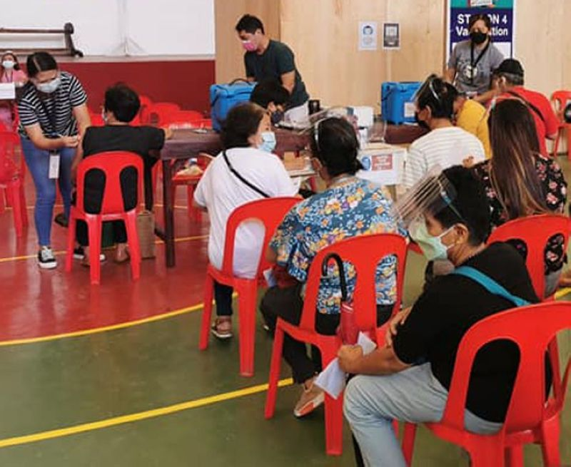 ZAMBOANGA. The City Health Office rolls out Wednesday, August 4, the vaccination of workers in local canning factories that fall under the A4 priority group at the gymnasium of the Zamboanga Peninsula Polytechnic University. A photo handout shows a nurse injecting a vaccine to a factory worker while the others wait for their turn to be vaccinated. (SunStar Zamboanga)