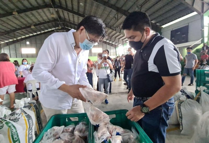FOOD DONATION. Former Candaba Mayor Danilo Baylon (L) shows Floridablanca Vice Mayor Mike Galang the food donation consisting of chicken, eggs and rice given to 3,300 solo parents and PWDs during Friday's distribution at the Floridablanca Sports Complex. (Chris Navarro)