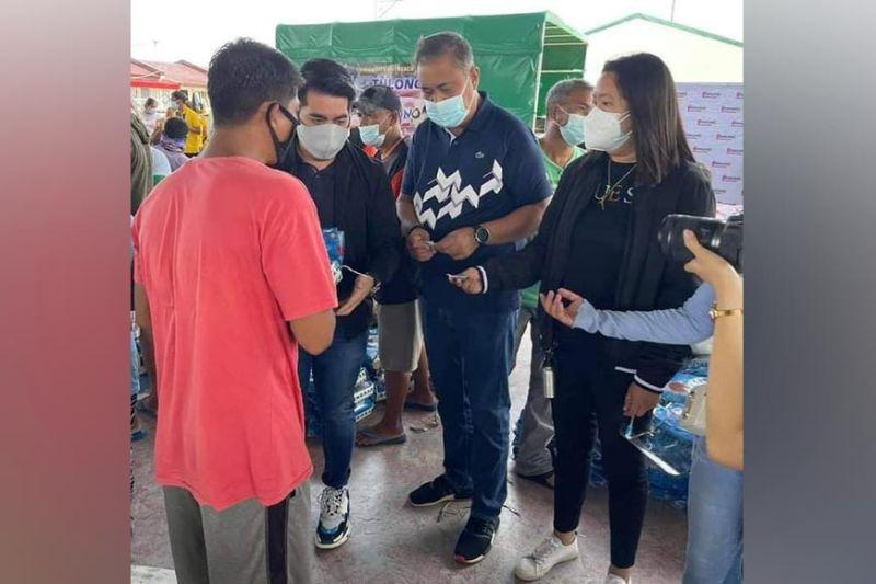 TULONG NI PINUNO. Pinuno representative Ivan Howard Guintu, Mayor Danilo Guintu and 1st Councilor Liezle Guintu lead the distribution of food packs to flood-affected Masantoleños. (Princess Clea Arcellaz)