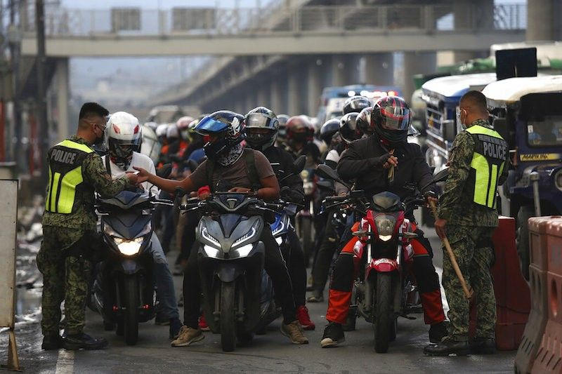 MANILA. Policemen wearing protective equipment inspect motorcycle riders at a checkpoint during a stricter lockdown as a precaution against the spread of the coronavirus disease at the outskirts of Marikina City on August 6, 2021. (AP)