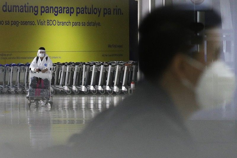 MANILA. In this photo taken in March 2021, a woman wearing a protective suit pushes a cart at the arrival area of the Ninoy Aquino International Airport. (File)