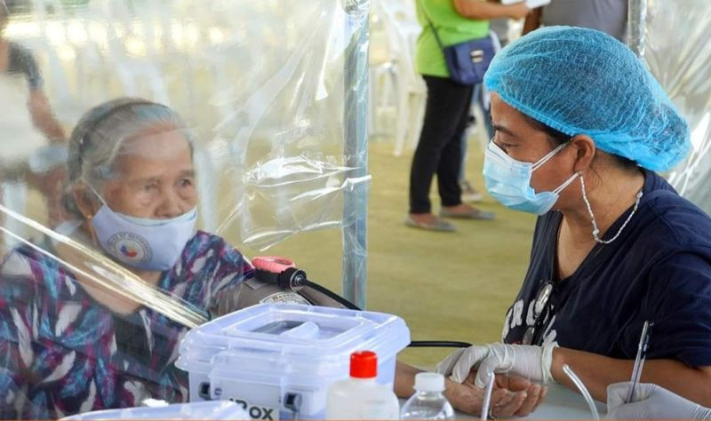 BEFORE THE JAB. A health worker in Apalit town checks on the condition of a senior citizen prior to vaccination. (Contributed photo)