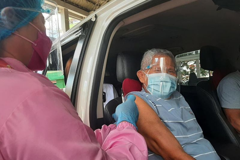 DRIVE THRU JABBING. Without stepping down from his vehicle, a senior citizen in Candaba town gets his first jab of Pfizer Covid-19 vaccine through the drive-thru vaccination at the Candaba Trade Center. (Princess Clea Arcellaz)