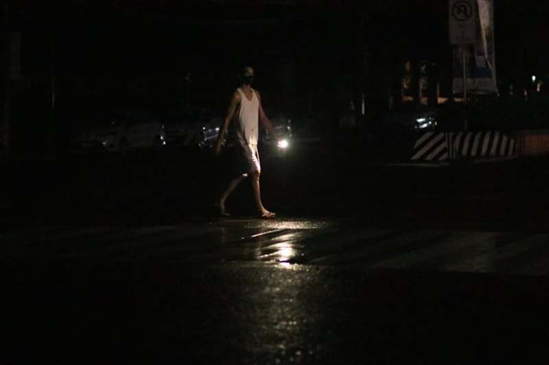 A walk in the dark. A man uses his cellular phone's flashlight to light his way along Osmeña Blvd. as Cebu City and most of Cebu were plunged into darkness by a power outage late Friday night, Aug. 20, 2021. The power interruption lasted until dawn of Saturday in some areas. All power in Cebu was finally restored by 4:30 a.m. Energy Secretary Alfonso Cusi has urged the Energy Regulatory Commission to investigate the incident. Officials of the Electric Power Industry Management Bureau and the Department of Energy also met on Saturday to discuss what happened. (AMPER CAMPAÑA)