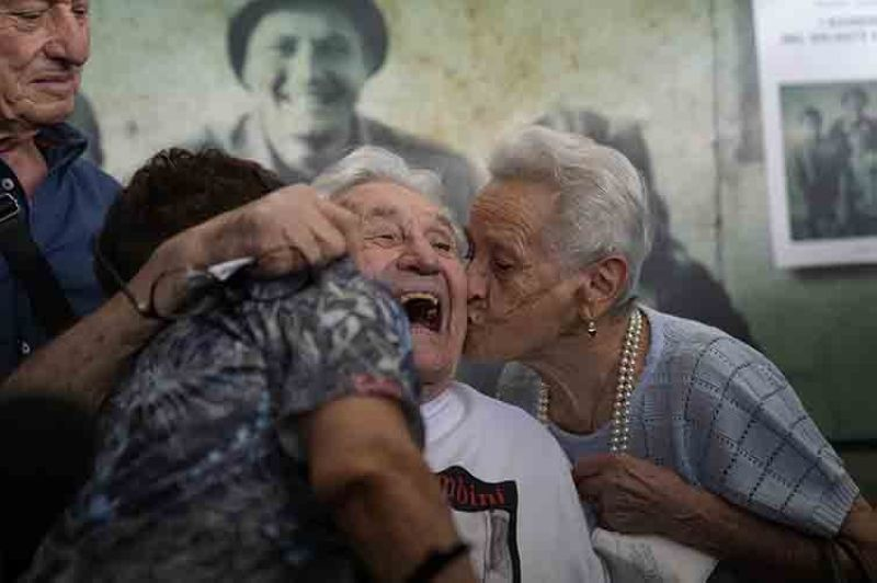 A 97-year-old retired American soldier Martin Adler, center, receives a kiss by Mafalda, right, and Giuliana Naldi that he saved during a WWII, at Bologna's airport, Italy, Monday, Aug. 23, 2021. For more than seven decades, Martin Adler treasured a black-and-white photo of himself as a young soldier with a broad smile with three impeccably dressed Italian children he is credited with saving as the Nazis retreated northward in 1944. The 97-year-old World War II veteran met the three siblings -- now octogenarians themselves -- in person for the first time on Monday, eight months after a video reunion.  (AP Photo/Antonio Calanni)
