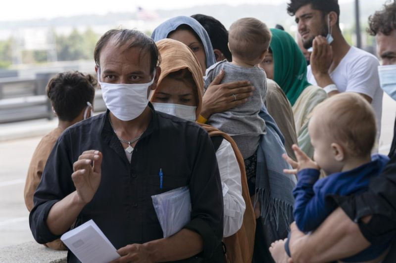 AFGHANISTAN. Families evacuated from Kabul, Afghanistan, wait outside the terminal to board a bus after arriving at Washington Dulles International Airport, in Chantilly, Va., Monday, August 23, 2021. (AP Photo)