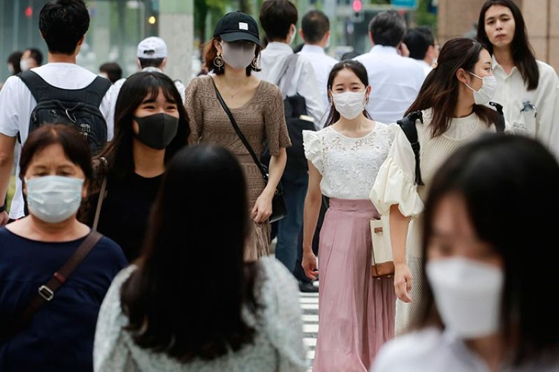 JAPAN. People wearing face masks to help protect against the spread of the coronavirus walk across an intersection Tuesday, August 24, 2021. (AP)