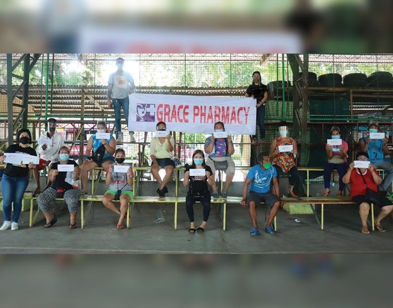 NEGROS. The fire victims in Purok San Jose Paho, Barangay Alijis, Bacolod City receive additional cash assistance from the Negros Grace Pharmacy Thursday, August 26, 2021. (Contributed photo)