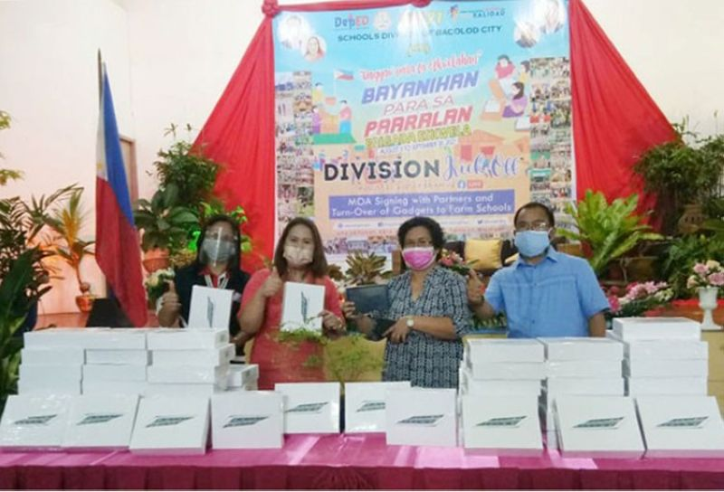 BACOLOD. Bacolod City Division Superintendent Gladys Amylaine Sales, CESO VI (2nd from left), turns over tablet units to Alangilan National High School OIC-Principal Veneranda (2nd from right) during the Brigada Eskwela 2021 opening rites at the Social Hall of the Bacolod City Division. Also in the photo are CID chief Dr. Janalyn Navarro and Assistant Superintendent Peter Galimba. (Jerome Galunan Jr.)