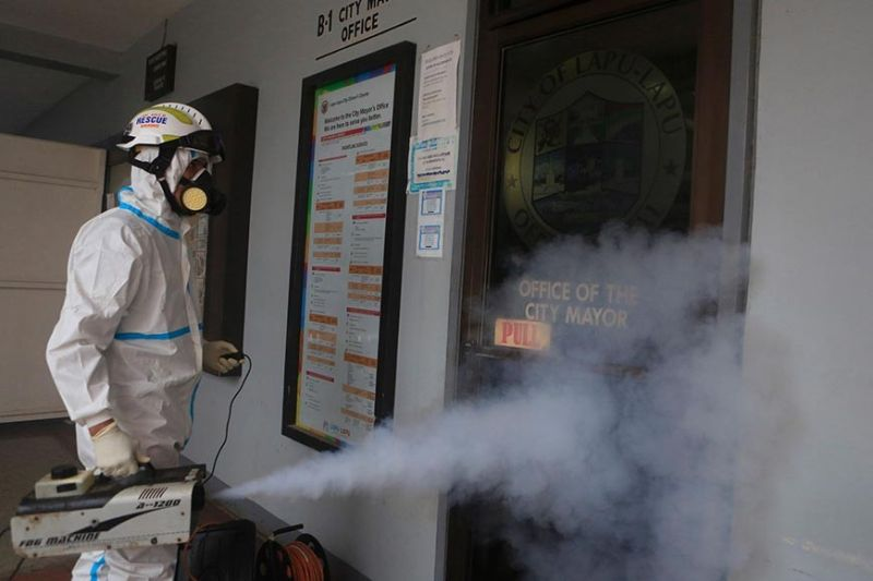 SECOND YEAR. A man disinfects the mayor's office in Lapu-Lapu City, Cebu on Aug. 26, 2021. Work was suspended at the Lapu-Lapu City Hall after 15 employees tested positive for Covid-19. Men in protective suits have become a common sight as the Covid-19 pandemic drags on well into its second year. / ALAN TANGCAWAN