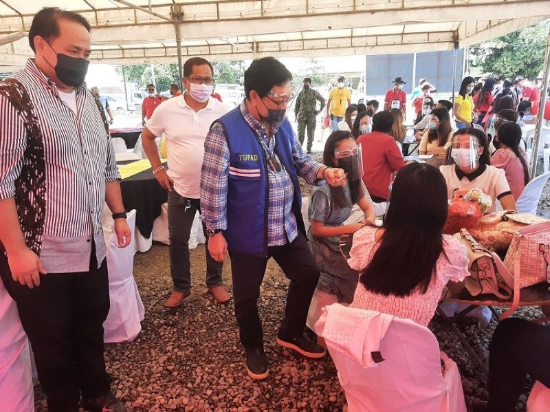 DOLE Secretary Silvestre Bello III greets Candabeño youth during his visit on Thursday in Candaba for a Tupad payout. With him is Governor Dennis Pineda. (Princess Clea Arcellaz)