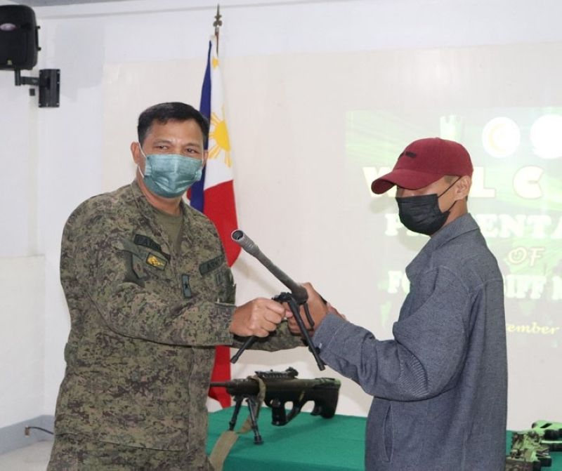 SURRENDER. Four followers of the Bangsamoro Islamic Liberation Front (BIFF)-Karialan faction surrender Wednesday, September 1, 2021, to military authorities in the province of Maguindanao. A photo handout shows one of the four BIFF surrenderers handing over a rifle to Brigadier General Ignatius Patrimonio, 1st Brigade Combat Team commander. (SunStar Zamboanga)