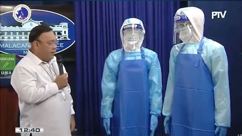 MANILA. Presidential Spokesperson Harry Roque Jr. shows the parts of a set personal protective equipment similar to those procured by the PS-DBM for the Department of Health. (Screenshot from state-owned PTV)