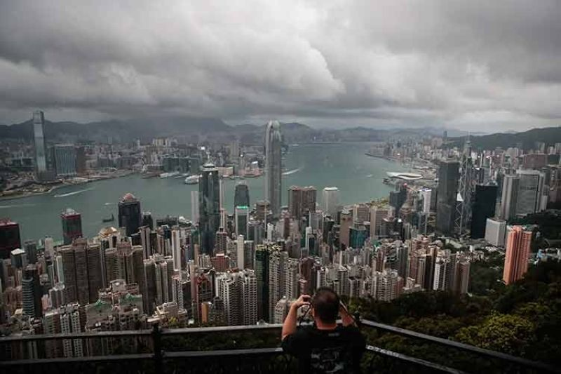 CHINA. In this September 1, 2019, file photo, a visitor sets up his camera in the Victoria Peak area to photograph Hong Kong's skyline. (AP)