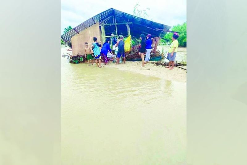 JOLINA EFFECT. Residents in Barangay Busogon, San Remigio, northern Cebu gather outside a house damaged by flood brought about by typhoon Jolina Tuesday, Sept. 7, 2021. (SAN REMIGIO DRRMO)