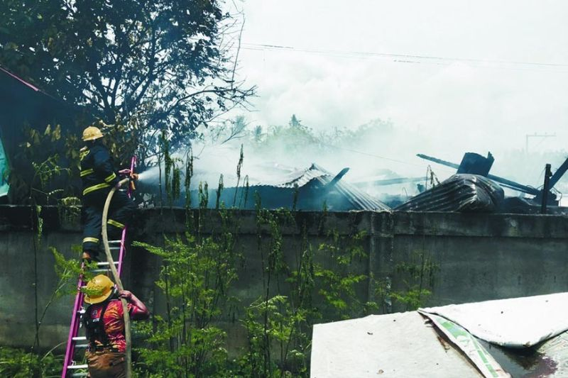 FIREFIGHT. Firefighters point their hoses at the burnt houses in Sitio Zone 2 in Barangay Biasong which were hit by a fire on Saturday morning, Sept. 11, 2021. / Talisay City government