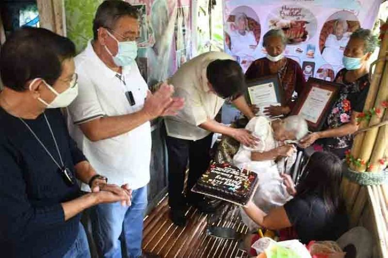 Oldest living person Francisca Susano (seated) receives plenty gifts from Senior Citizens' Commissioner Franklin Quijano (third from left), Kabankalan City Mayor Pedro Zayco (second from left) and Vice Mayor Raul Rivera (left) as she celebrates her 124th birthday at their house in Barangay Oringao in Kabankalan City on Saturday, September 11. (Contributed photo)