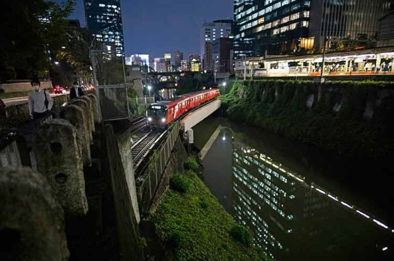 JAPAN. People wearing face masks walk along the Kanda River as a train passes by near a station in Tokyo, Thursday, September 9, 2021. (AP)