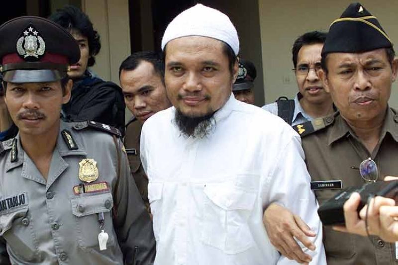 INDONESIA. Militant cleric Abu Rusdan (center) is escorted by security officers after his trial hearing at a district court in Jakarta, Indonesia, in this November 3, 2003 file photo. (AP)