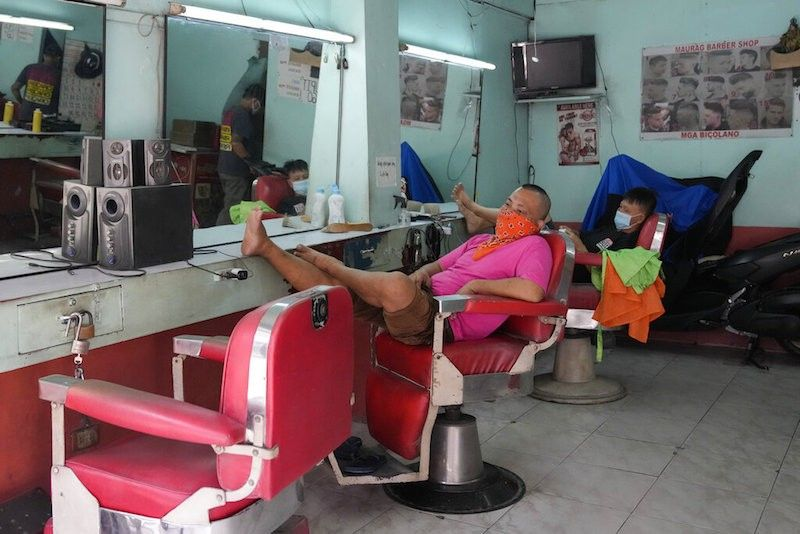 MANILA. Barbers wait for customers as they reopen their shop after the government has allowed some business establishments to operate with health restrictions on Thursday, Sept. 16, 2021 in Quezon City. (AP)
