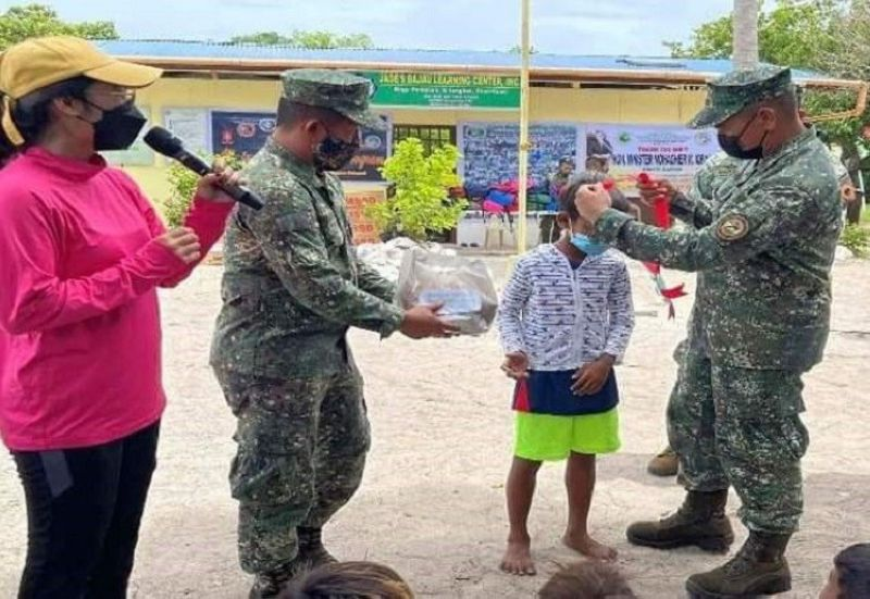 """BAYANIHAN. The Joint Task Force (JTF)-Tawi-Tawi together with the municipal government of Sitangkai conduct last week an """"All-In-One Bayanihan"""" activity in Pangguan village. A photo handout shows marine troops giving a hygiene kit to a Badjao child during the activity. (SunStar Zamboanga)"""