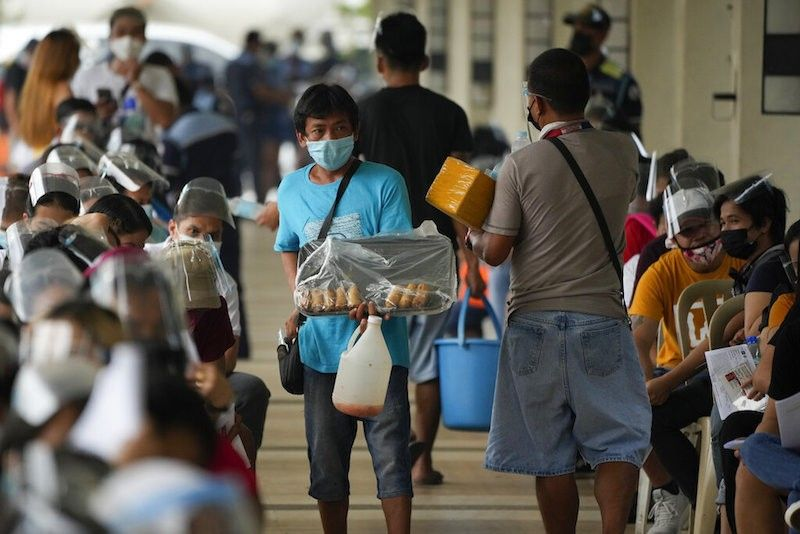 MANILA. Vendors sell food and water to waiting residents at a vaccination center in Quezon City on Sept. 13, 2021. (AP)