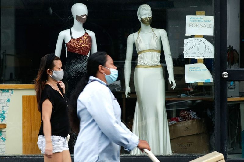 OUTLOOK. Women walk past mannequins wearing face masks advertised for sale at a shop in Makati City. Asian Development Bank-Philippines expects the country to grow 7.1 percent in 2021, falling to 5.4 percent in 2022. / AP