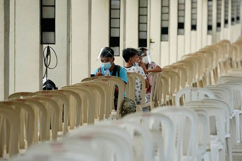 MANILA. People rests on vacant seats at a vaccination center in Quezon City, Philippines on September 13, 2021. (AP)