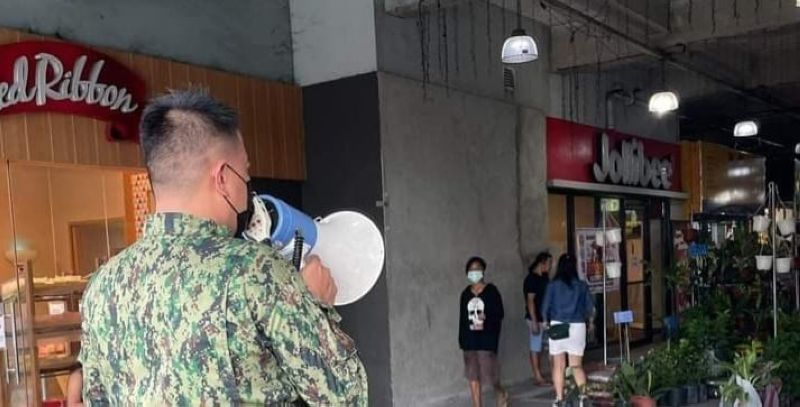 A policeman reminds the mall-goers in Bacolod City to wear their face masks. (Contributed Photo)
