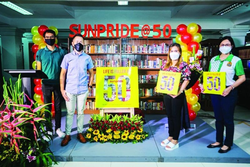 """GOLDEN YEAR. Sunpride celebrated its 50th year through a ceremonial turnover and unveiling of its commemorative book, """"Life is Fuller at 50: Retracing Sunpride's Proud Legacy."""" From left, Sunpride's marketing team leader Bryan Astrolabio, Sunpride's marketing head Don Hanley Wong, Mandaue City Public Library chief librarian Angelina Cagatulia and Cebu City Public Library staff member Sharon Jakosalem, representing chief librarian Rosario Chua. / SUNPRIDE"""
