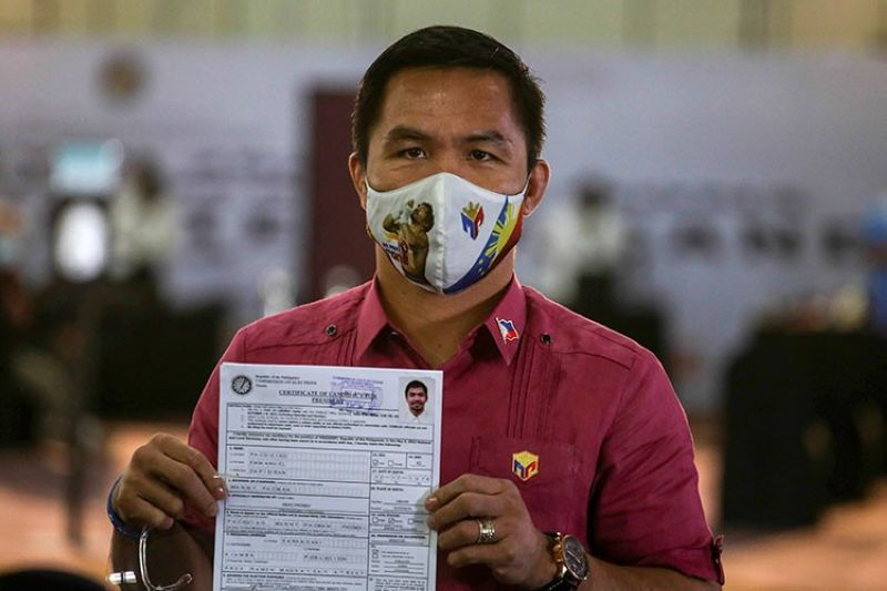 MANILA. Retired Filipino boxing star and Senator Manny Pacquiao shows his certificate of candidacy for next year's presidential elections shortly after filing before the Commission on Elections at the Sofitel Harbor Garden Tent in Manila, Philippines on Friday, October 1, 2021. (AP)