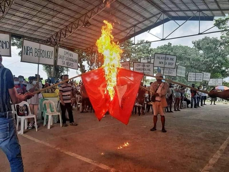 NEGROS. Flag replicas of the Communist Party of the Philippines-New People's Army were burnt during a peaceful assembly of farmers at Barangay E. Lopez in Silay City, Negros Occidental Saturday, October 2. (Contributed photo)