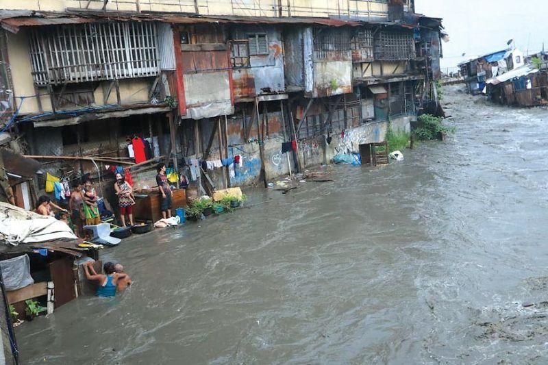 KUYAW: Dihang nagbunok ang uwan mga semana kapin ang nakalabay, pipila ka mga balay sa daplin sa Kinalumsan River sa Barangay Mambaling, Dakbayan sa Sugbo nameligro. Tungod sa hulga sa baha, ang Cebu City nagpalawom sa kasapaan gikan sa ubos padung sa ibabaw. / AMPER CAMPAÑA