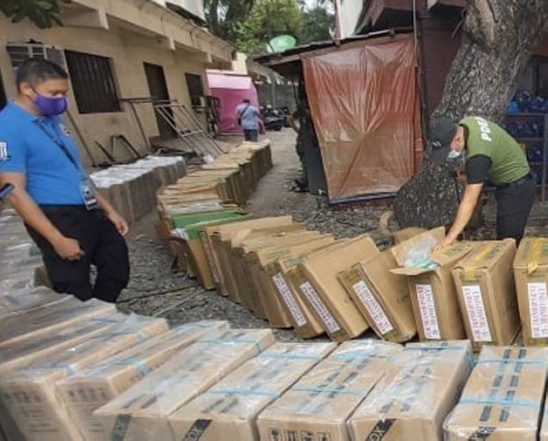 SMUGGLED CIGARETTES SEIZED. Government operatives seized a shipment of some P4.7 million worth of smuggled cigarettes and arrested eight people on Friday, October 8, near Manalipa, an island village east of Zamboanga City. A photo handout shows a K9 of the Philippine Drug Enforcement Agency and a Bureau of Customs personnel inspecting the seized cargo for possible presence of illegal drugs. (SunStar Zamboanga)