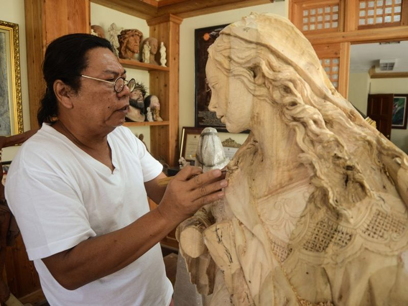 ARTIST AT WORK. Kapampangan Ecclesiastical artist Wilfredo Layug works on a wooden image sculpture of the Virgin Mary in his shop in Betis, Guagua, Pampanga. (Photo courtesy of Ruston Banal)