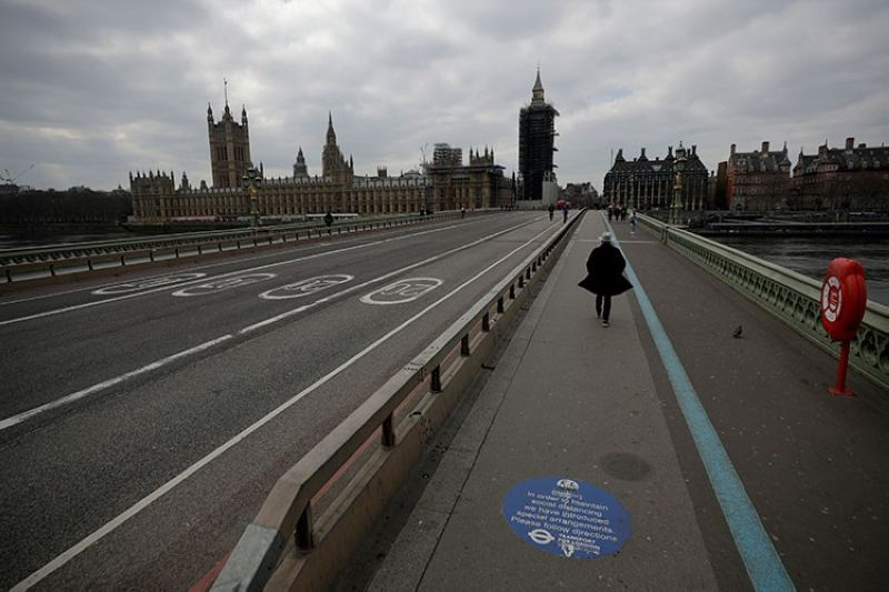 LONDON. In this March 23, 2021 file photo, people pass over a quiet Westminster Bridge, backdropped by the scaffolded Houses of Parliament and the Elizabeth Tower, known as Big Ben, in London, during England's third coronavirus lockdown. (AP)