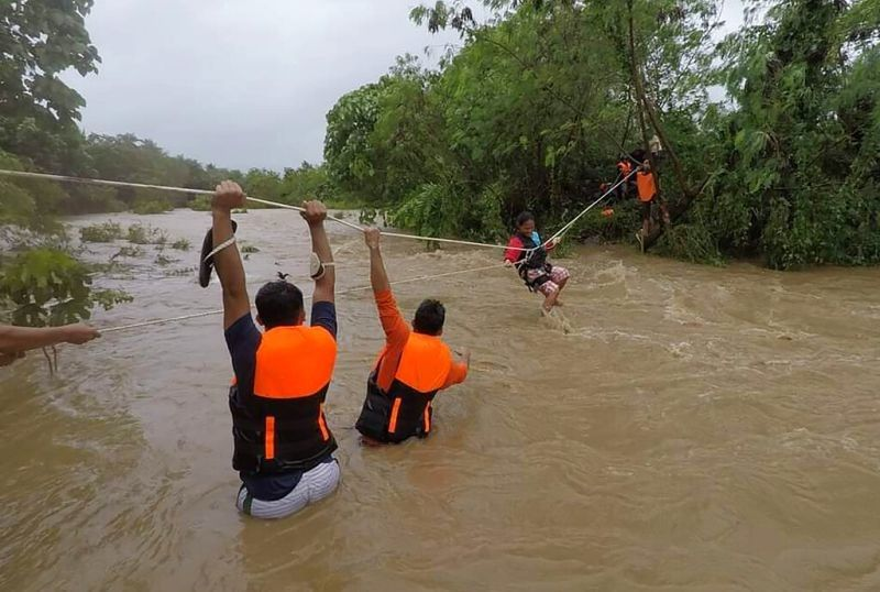 MANILA. In this photo released by the Gonzaga Municipal Disaster Risk Reduction and Management Office, a resident is pulled along a rope as rescuers wait on the other side of a swollen river caused by heavy rains from Tropical Storm Kompasu in Gonzaga town, Cagayan Province on Oct. 11, 2021. (Gonzaga MDRRMO via AP)
