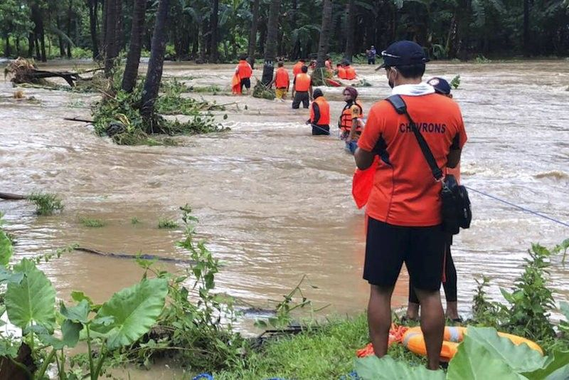 MANILA. In this handout photo provided by the Philippine Coast Guard, rescuers help residents navigate floodwaters caused by Tropical Storm Maring (Kompasu) in Brooke's Point, Palawan on Tuesday Oct. 12, 2021. (Philippine Coast Guard via AP)
