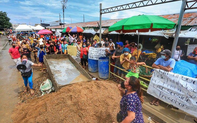TENSYON: Nagtinubagay kining duha ka mga babayeng vendor sa Carbon public market dihang nag-rally ang mga manindahay nga pabor sa modernisayon sa merkado sa Biyernes, Oktubre 15, 2021. / Amper Campaña