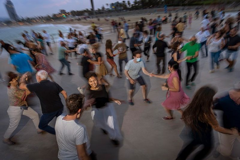SPAIN. People dance on a promenade facing the Mediterranean Sea as the sun sets at a beach in Barcelona, Spain, Sunday, October 3, 2021. (AP)