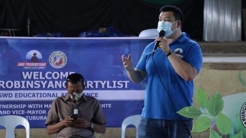 NAMULONG: Si Congressman Alfred Delos Santos (nagbarog) sa Ang Probinsyano Partylist namulong atol sa pagpanghatag og financial assistance sa mga bata sa Tuburan kagahapon, Oktubre 18. / Tampo
