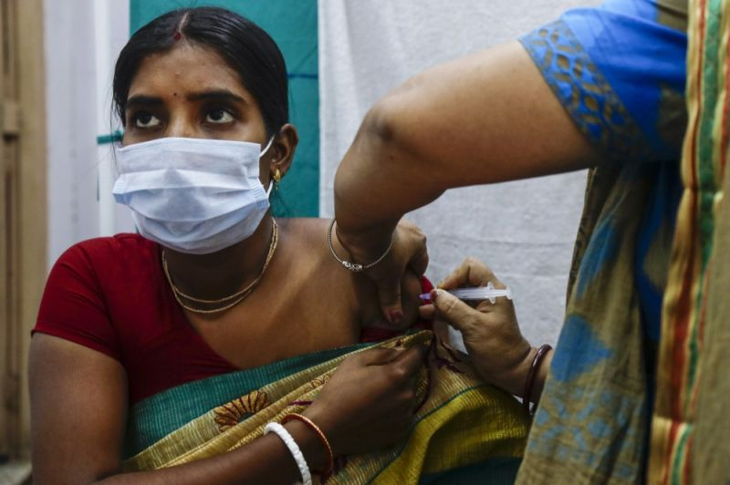 A health worker administers a dose of Covaxin Covid-19 vaccine at a health center in Garia , South 24 Pargana district, India, Thursday, Oct. 21, 2021. India has administered 1 billion doses of COVID-19 vaccine, passing a milestone for the South Asian country where the delta variant fueled its first crushing surge this year. (AP Photo)